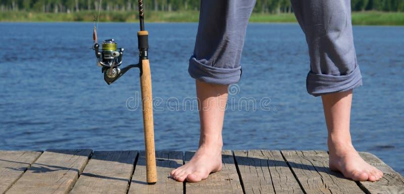 Gerät für fangende Fisch- und Mannfüße, auf dem Hintergrund des Piers auf dem Teich stockfotos