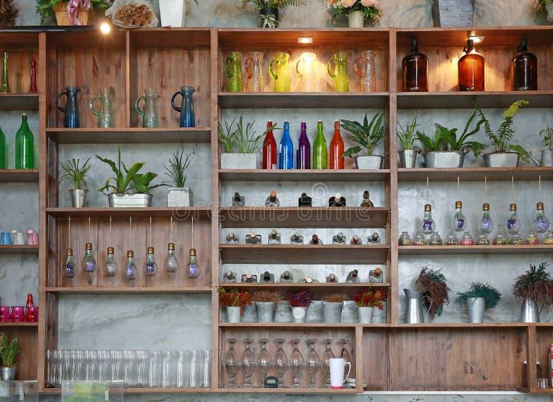Geräte auf Regalen des Cafés Flaschen, Blume, Glas, Gläser und Baum stockfotos