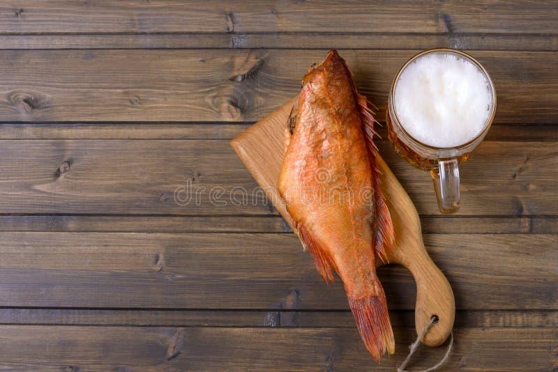 Geräucherte Fische und frisches Bier auf Holztisch lizenzfreie stockfotos