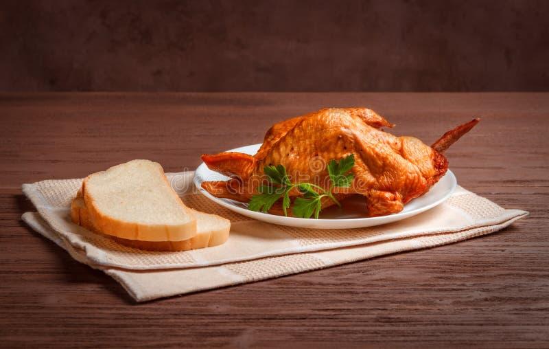 Geräucherte Hühnerflügel mit Brot in einer weißen Platte auf einer Serviette stockfotos