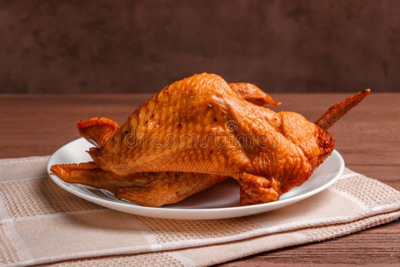 Geräucherte Hühnerflügel mit Gewürzen in einer weißen Platte auf einer Serviette lizenzfreies stockfoto