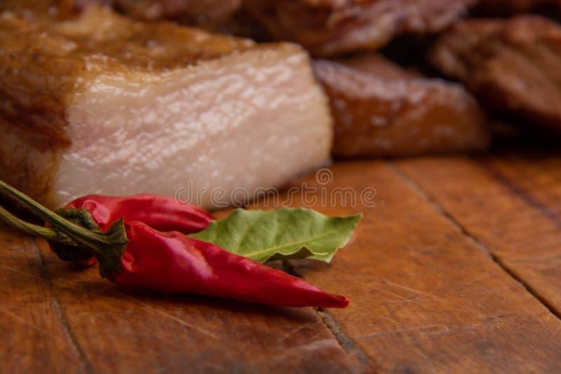 Geräucherte Schweinefleischrippen, geschnittenes Schweinefett, Fleisch und rotes Papier auf hölzernem Brett stockfotografie