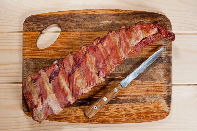Geräucherte Schweinefleischrippen saftig und fleischig auf einem hölzernen Schneidebrett stockbild