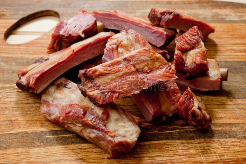 Geräucherte Schweinefleischrippen saftig und fleischig auf einem hölzernen Schneidebrett lizenzfreies stockfoto