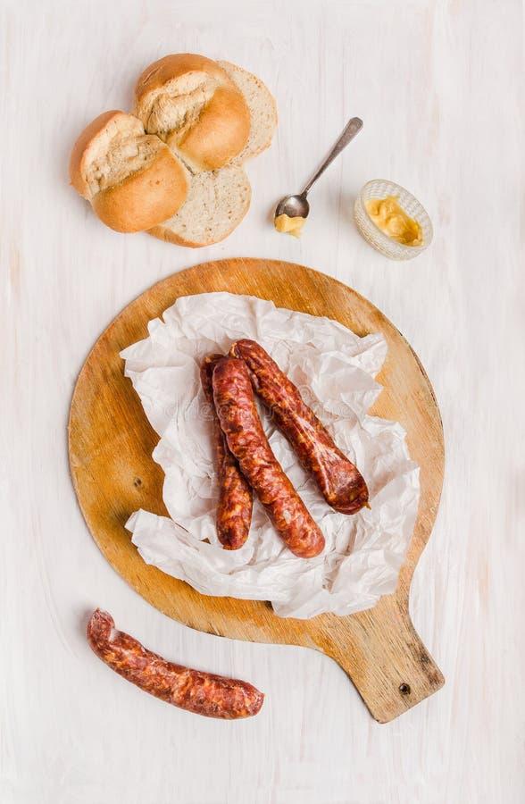 Geräucherte Wurst in papier auf Schneidebrett mit Brot und Senf lizenzfreie stockfotos