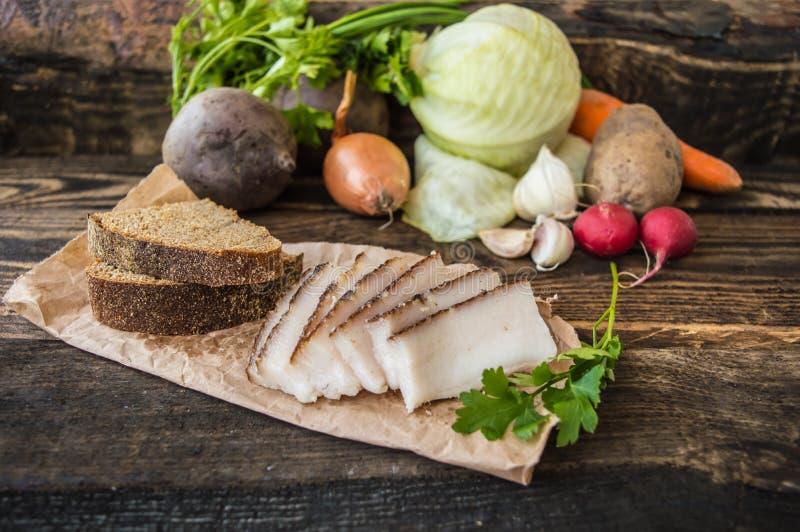 Geräuchertes Schweinefett mit Brot und Gemüse im Hintergrund Hölzernes rustikales stockfoto
