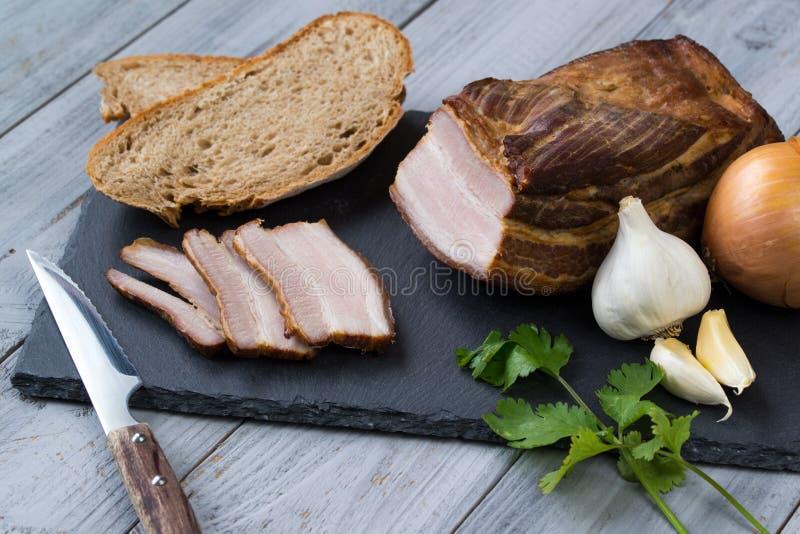 Geräuchertes Schweinefett mit Gemüse und Brot auf hölzernem Hintergrund lizenzfreies stockbild