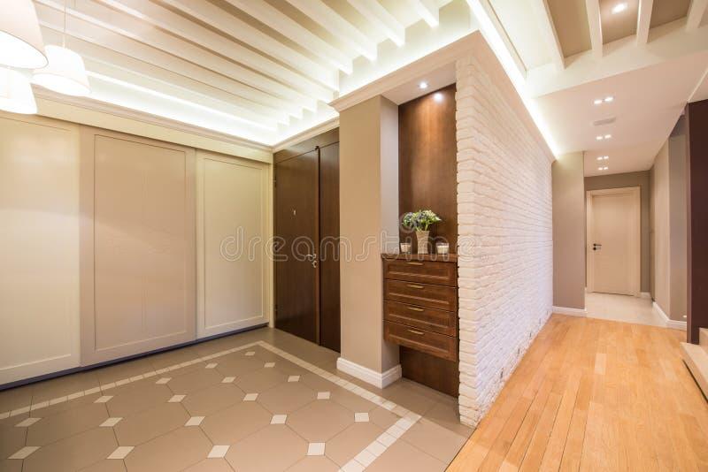 Geräumiger Vorzimmerinnenraum in den warmen Tönen und in modernem Decke ligh stockfotografie