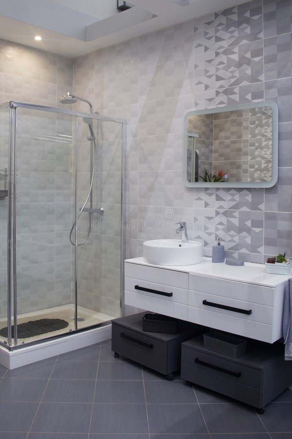 Geräumiges Badezimmer in den grauen Tönen mit erhitztem Boden, Dusche, große Wanne stockfotografie