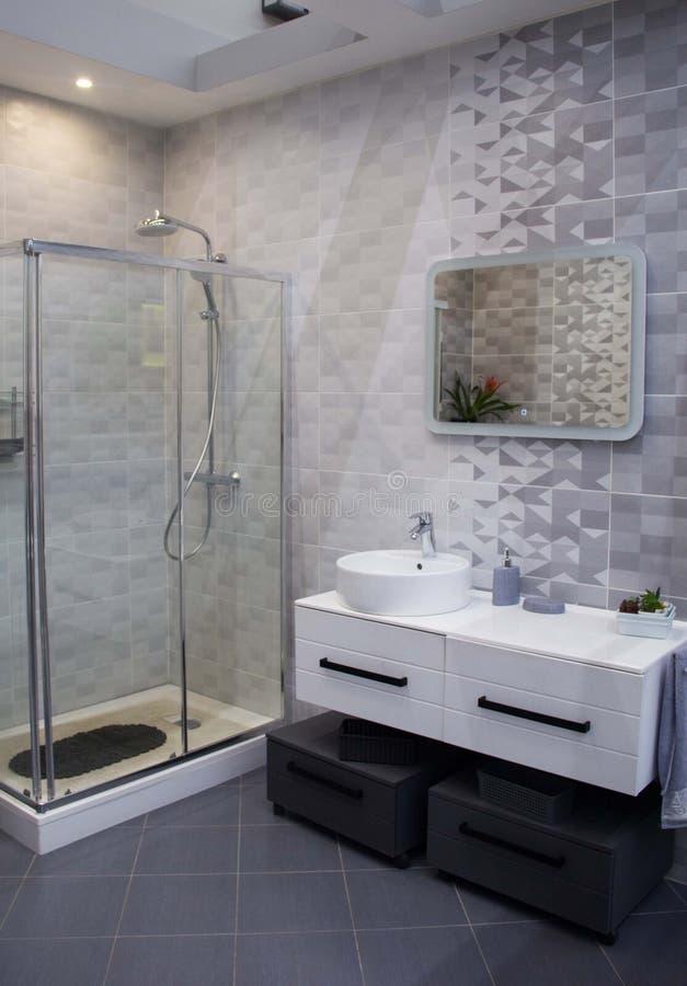 Geräumiges Badezimmer in den grauen Tönen mit erhitztem Boden, Dusche, große Wanne lizenzfreies stockfoto