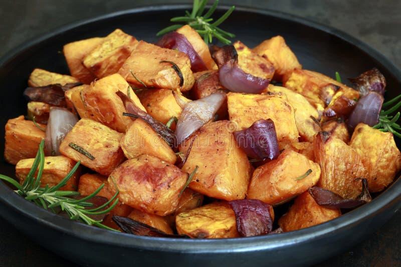 Geröstete Süßkartoffeln mit Roten Zwiebeln und Rosmarin in Black Dish lizenzfreie stockbilder