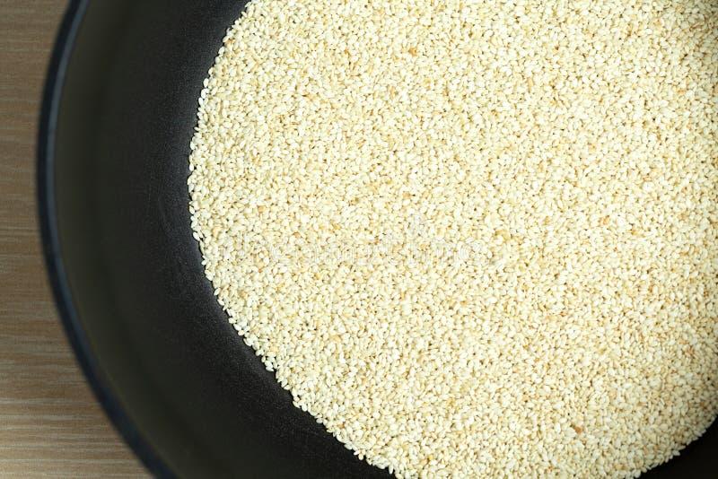 Geröstete Samen des indischen Sesams in einer Bratpfanne Gebratene Samennahaufnahme des indischen Sesams lizenzfreie stockbilder