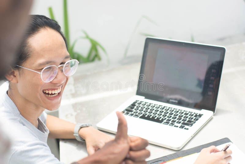 Ger coworkers upp tummen på vännen, den unga asiatiska mannen med exponeringsglas med bärbara datorn och anteckningsboken för att royaltyfri foto