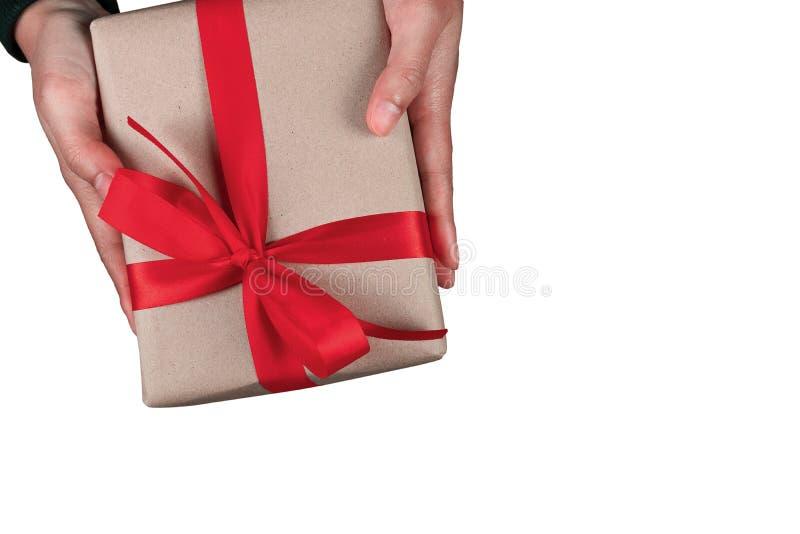 Ger den mänskliga manhanden för bonusen en närvarande brun fluga för gåvaask det röda bandet som isoleras på vit bakgrund med bäs royaltyfria foton