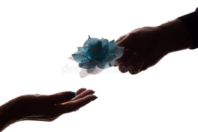 Ger den unga mannen för handen blomman till den äldre kvinnan - konturn, garnering arkivfoton