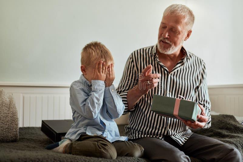 Geração avô e neto com a caixa de presente que senta-se no sofá em casa imagens de stock royalty free