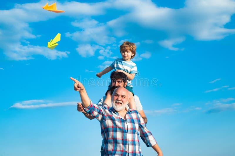 Geração de três homens Filho bonito com o jogo do paizinho exterior Dia de pais - o avô, o pai e o filho estão abraçando e fotografia de stock