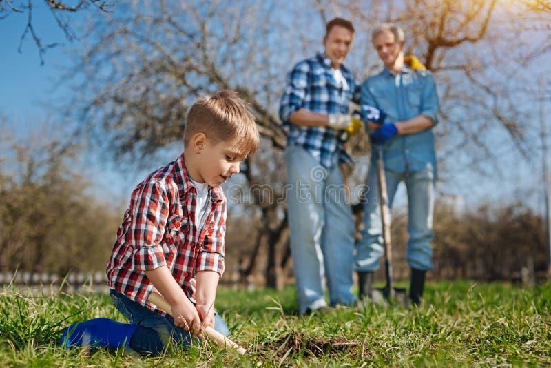 Geração mais velha que olha a terra de escavação da criança bonito imagens de stock royalty free