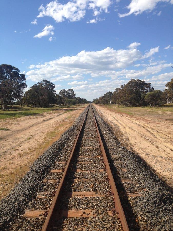 Gerade Bahnlinie, die durch australische Landschaft ausdehnt stockfotografie