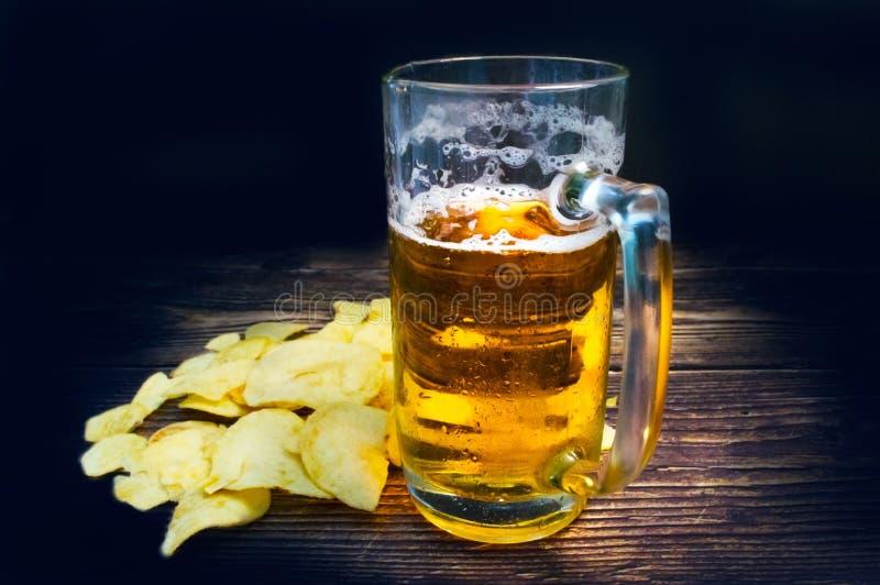 Gerade ein Glas Bier und Chips auf einem Weinleseholztisch stockfoto