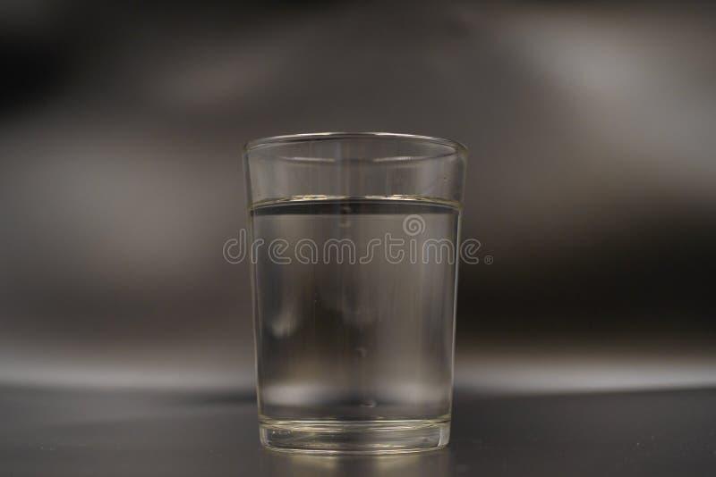 Gerade ein Glas Wasser auf einem dunklen Holztisch Mineralwasser in einem Glas auf einem schwarzen Hintergrund Ein Glas mit Wasse stockbilder