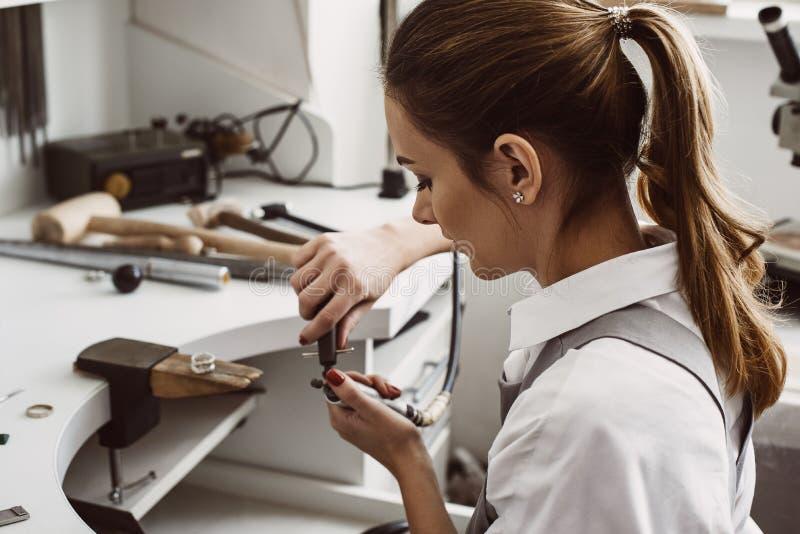 Gerade ein Moment Seitenansicht des weiblichen Juweliers die Werkzeuge für Arbeit mit silbernem Ring an ihrer Schmuckwerkstatt vo stockfoto