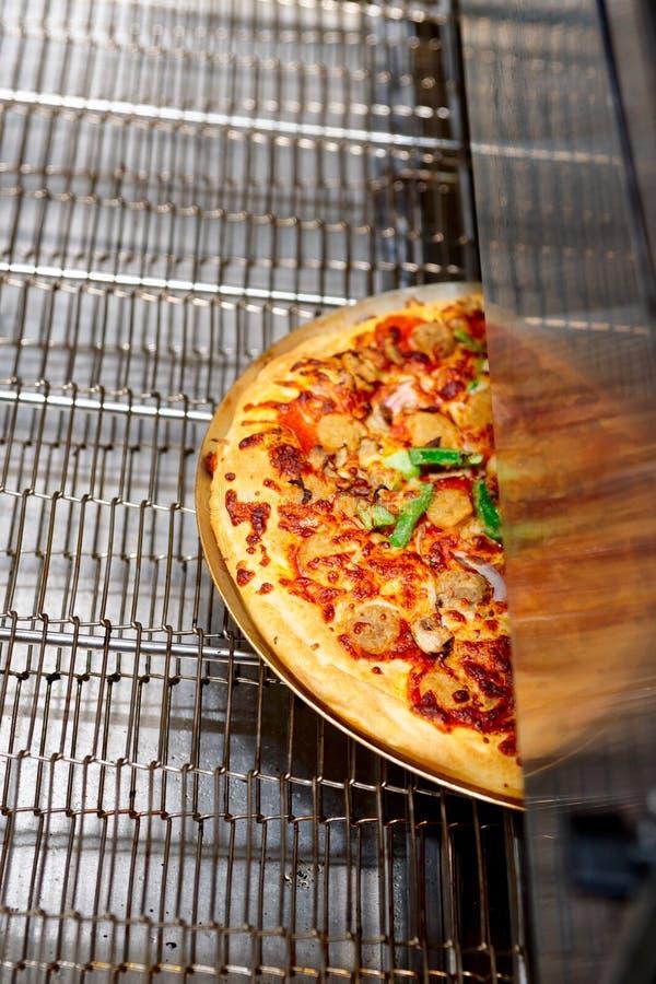 Gerade gebackene Pizza, die von einem Ofen kommt lizenzfreies stockbild