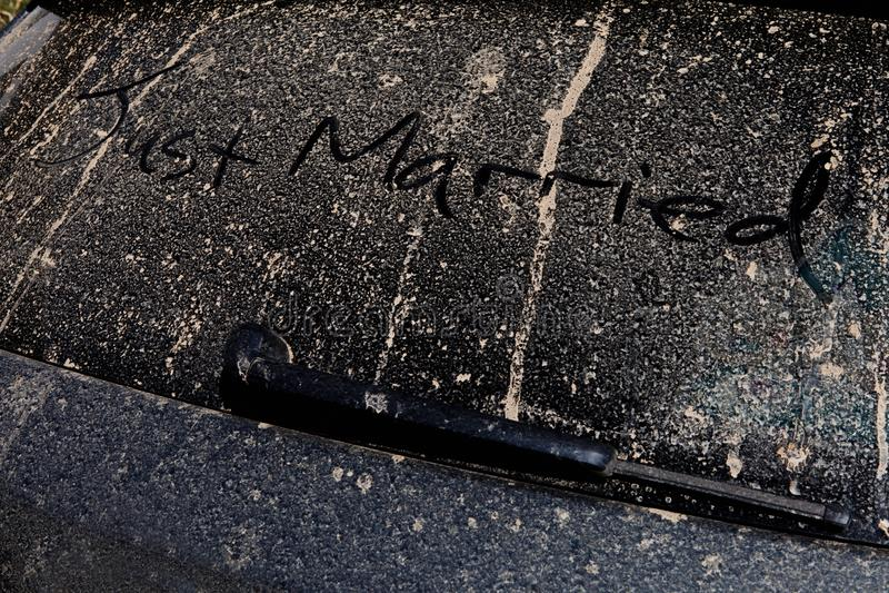 Gerade geheiratet eigenhändig angerissen auf der Rückseite eines schlammigen Autos auf einer Sonne lizenzfreies stockfoto