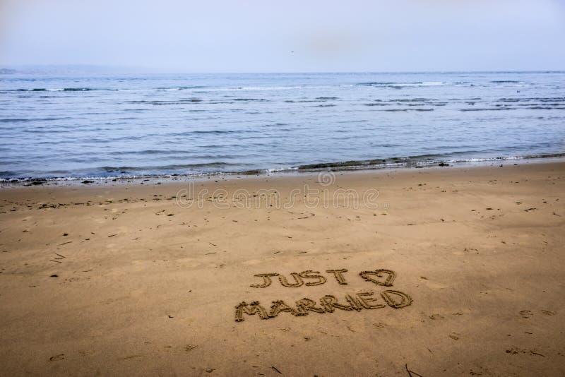 Gerade geheiratet geschrieben in den Sand lizenzfreies stockbild