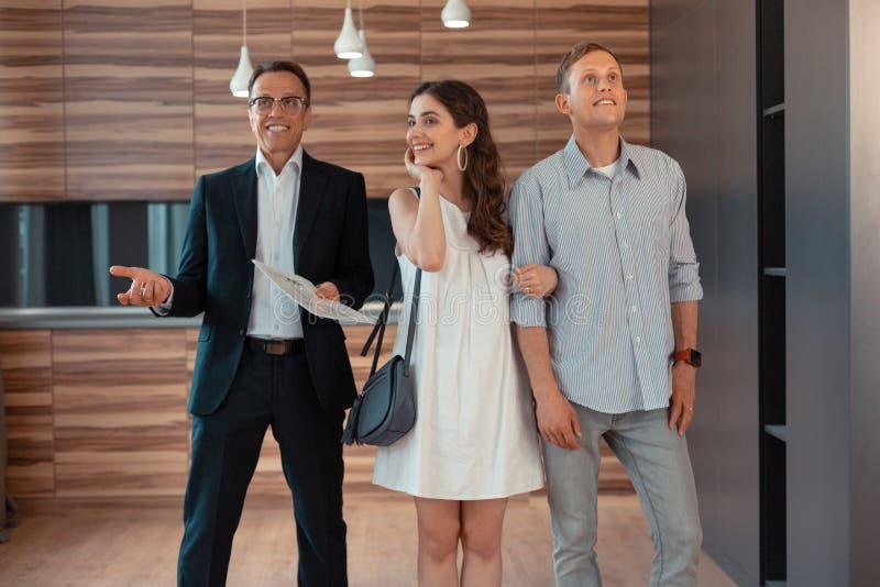 Gerade Kaufen-Hausstellung des verheirateten Paars nahe Immobilienagentur lizenzfreies stockfoto