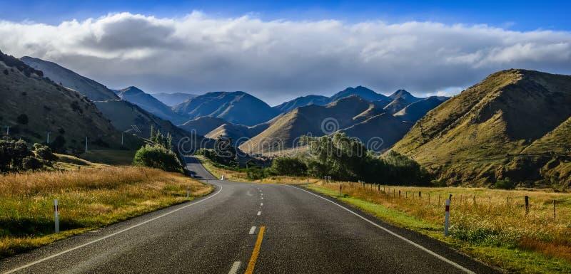 Gerade leere Straße im Berg, Neuseeland lizenzfreie stockfotos