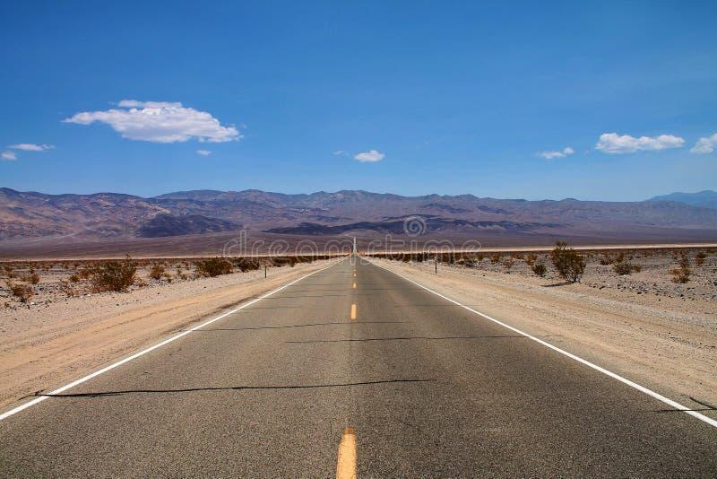 Gerade Straße durch eine flache Wüstenlandschaft, mit Hügeln und einem blauen Himmel stockbild