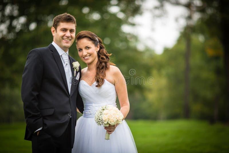 Gerade verheiratete, junge Hochzeitspaare in einem Park stockfoto