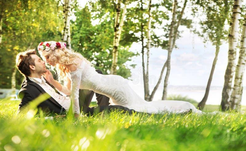 Gerade verheiratetes Paar, das auf der Wiese sich entspannt lizenzfreie stockbilder