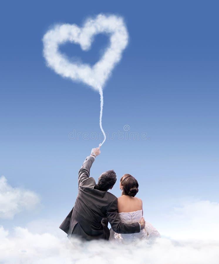 Gerade verheiratetes Paar, das auf der Wolke sitzt stockfoto