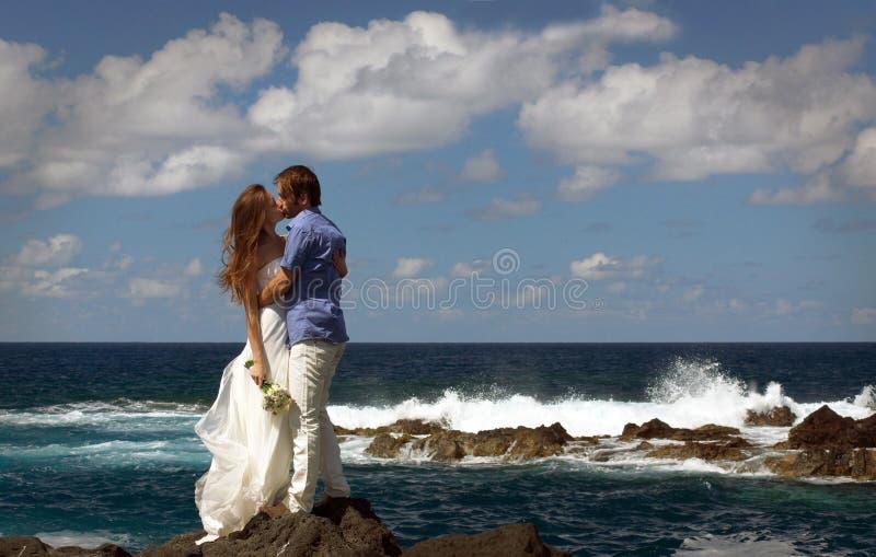 Gerade verheiratetes Paar, das auf Ozeanufer auf Flores-Insel, Azoren küsst stockfotografie