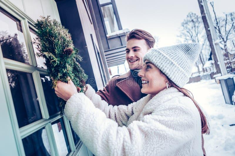 Gerade verheiratetes Paar, das draußen ihr Haus zum ersten Mal verziert lizenzfreies stockbild
