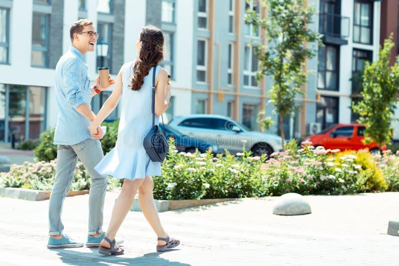 Gerade verheiratetes Paar, das Hand in Hand nach der Arbeit geht lizenzfreies stockbild