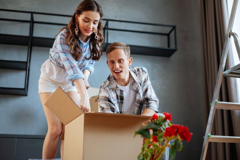 Gerade verheiratetes Paar, das Kasten beim Bewegen auf neues Haus auspackt stockfotografie