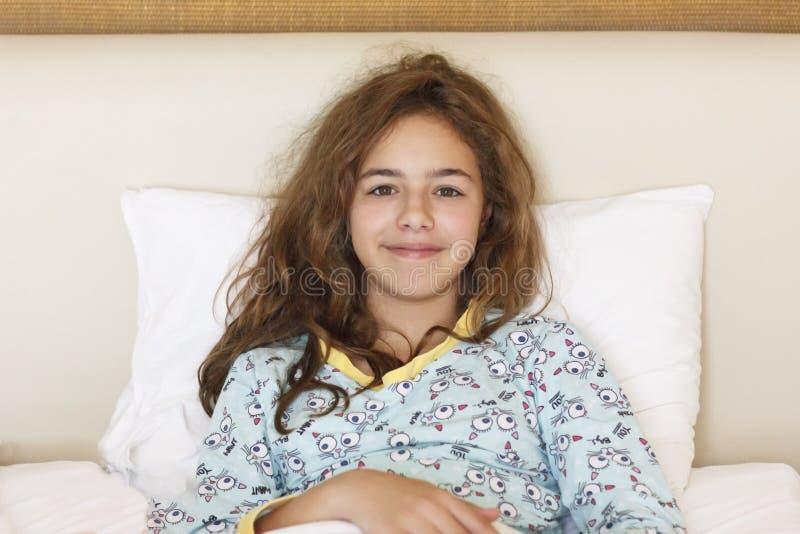Gerade waches hübsches Jugendlichmädchen mit lustigem Gefühlgesicht und dem wilden Haar auf dem Bett stockfotos
