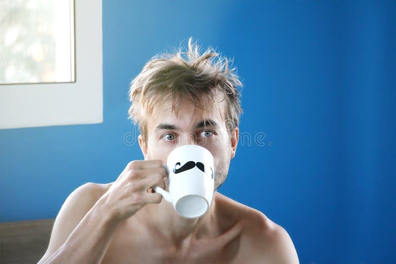 Gerade wachte auf und zerzauste den Mann, der frischen Kaffee oder Tee vom Becher mit dem gemalten schwarzen Schnurrbart, gutem W stockfoto