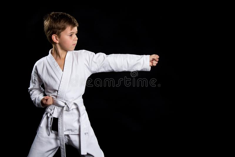 Gerader linker Handfaustschlag, Haltung im Karate Kind im Kimono auf dem schwarzen Hintergrund lizenzfreie stockfotos