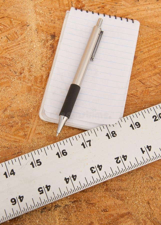 Gerader Rand, Notizblock und Stift auf Furnierholz stockbild