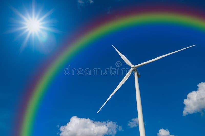 Gerador de poder da turbina eólica do close up com o arco-íris no céu azul foto de stock royalty free