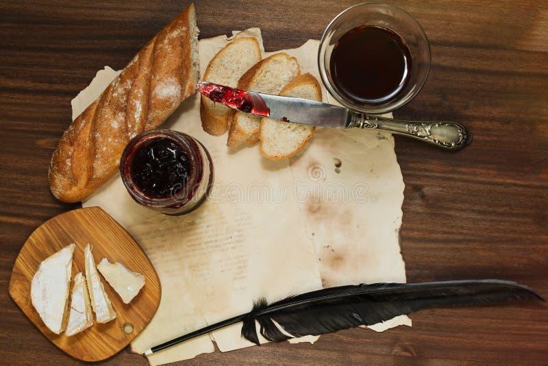 Geraffineerd stilleven van rode wijnglas, camembertkaas, baguette stock afbeeldingen