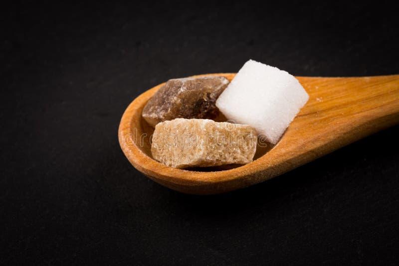 Geraffineerd wit en bruine suiker in houten lepel royalty-vrije stock foto's