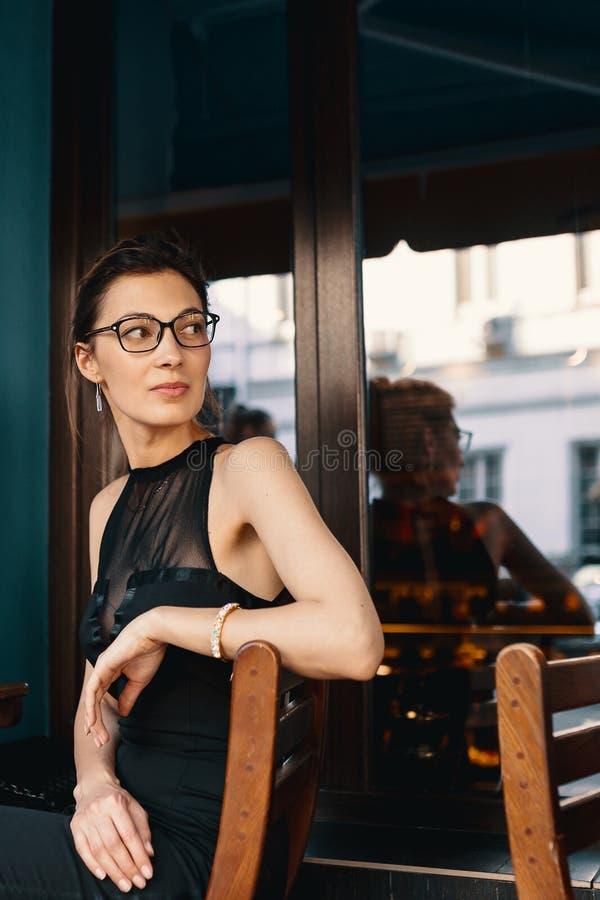 Geraffineerde bedrijfsvrouw in rondgedraaide glazen, zag zij somebody terwijl het zitten in een koffie stock afbeeldingen