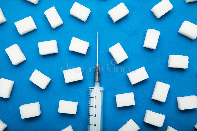 Geraffineerde suiker en een spuit op een blauwe achtergrond Het concept het bestrijden van bovenmatige consumptie van suiker, die royalty-vrije stock foto's