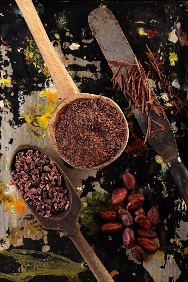 Geraspte chocolade, ruwe cacaobonen, verscheurde chocolade en cacao B royalty-vrije stock fotografie