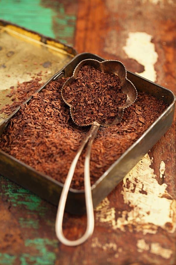 Geraspte donkere chocolade in uitstekend tin stock foto